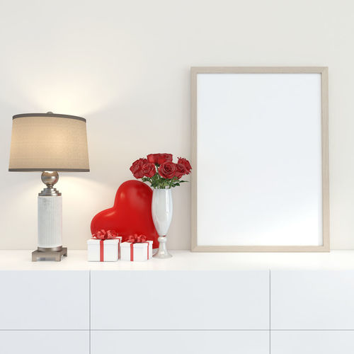 Red and white vase on table against wall at home