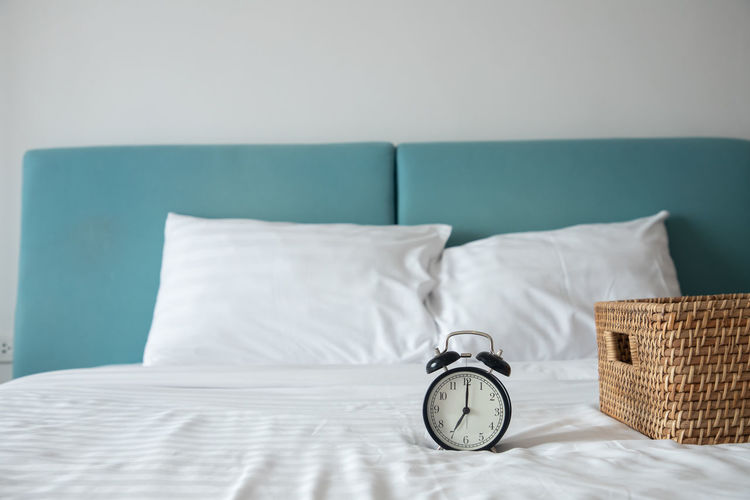 Clock by wicker basket on bed at home