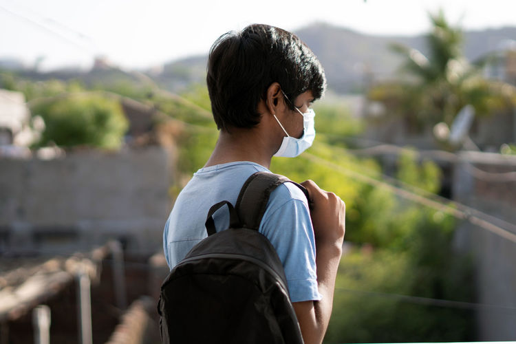 Rear view of boy standing against railing