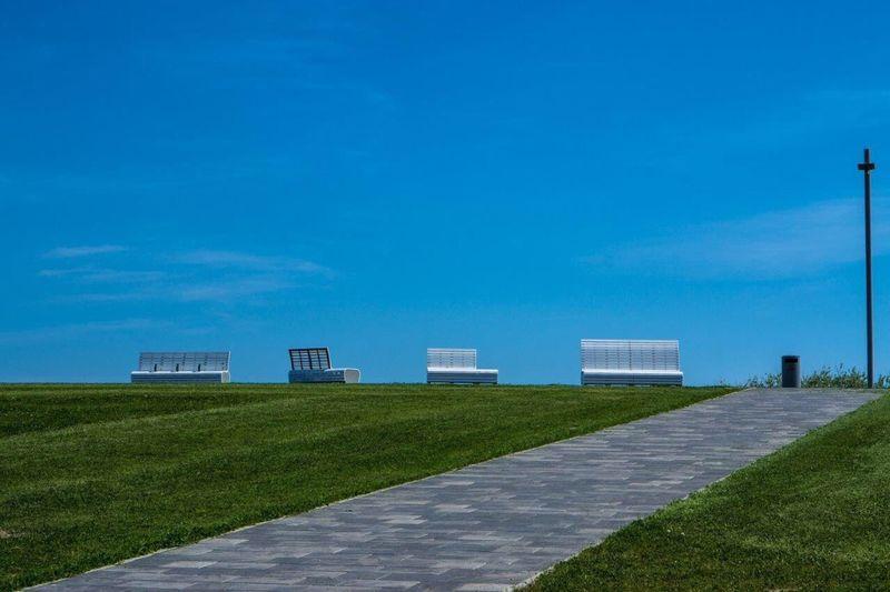 Empty footpath amidst grassy field against blue sky