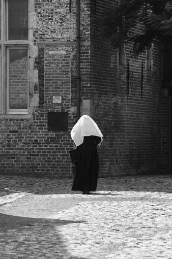 Real People Rear View One Person Built Structure Architecture Full Length Walking Building Exterior Asian Style Conical Hat Women Day Outdoors Lifestyles Under Tree Adult People Nun Religion Habit Church Leuven