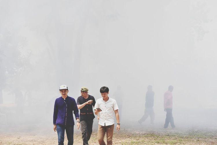 Men walking on field during foggy weather