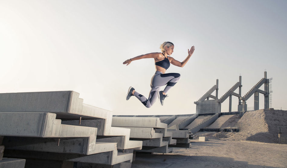 Middle Eastern Girl with short braided hair jumping of a stack of blocks on a construction site wearing gray and black fitness outfit on a hot bright sunny day. Exercising Jumping Off Rocks Sitting Architecture Bright Day Day Dusty Effort Fitness Model Full Length Hot Day ☀ Human Arm Jumping Leisure Activity Lifestyles Mid-air Middle Eastern Woman Motion Nature One Person Outdoors Real People Side View Sky Sport Sports Clothing Stretching Teenager Vitality Young Adult Young Women