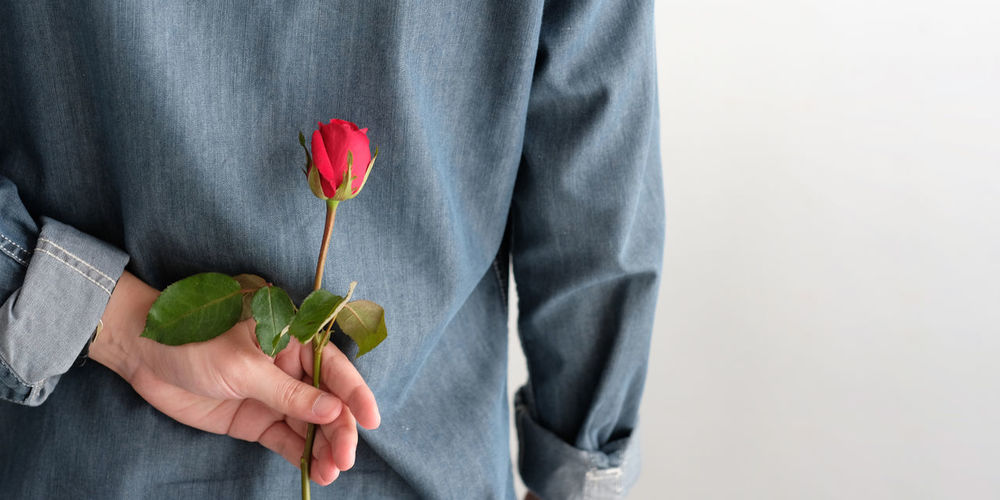 Midsection of man holding rose against gray background