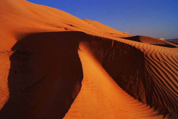 Sunlight falling on desert against blue sky