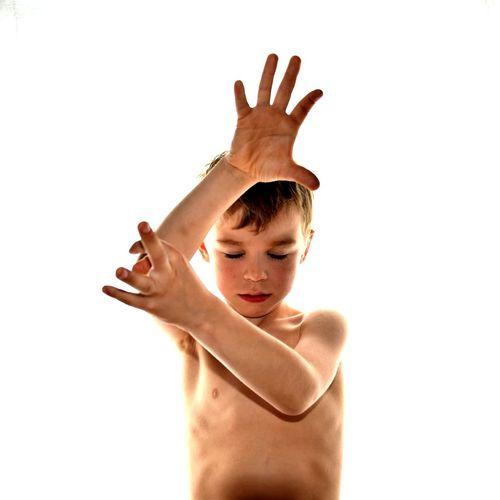 Shirtless boy gesturing against white background