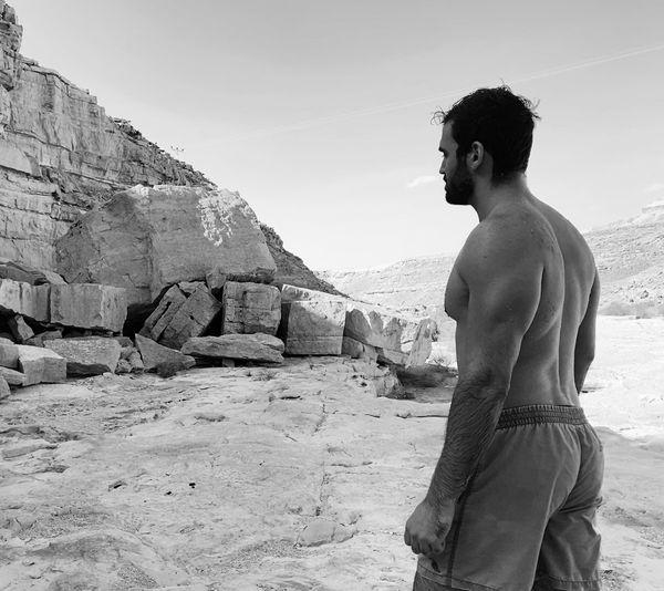 Rear view of shirtless man standing on rock