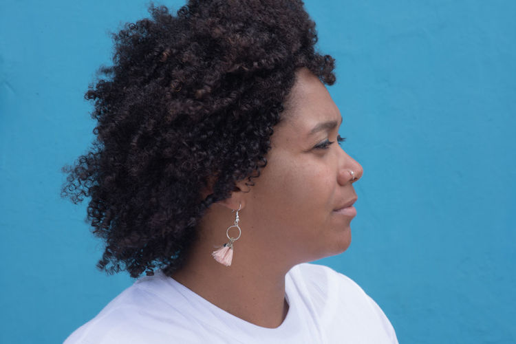 Blue Headshot Portrait One Person Curly Hair Blue Hairstyle Lifestyles Leisure Activity Looking Real People Hair Young Adult Jewelry Black Hair Women Looking Away Casual Clothing Young Women Contemplation Blue Background Profile View