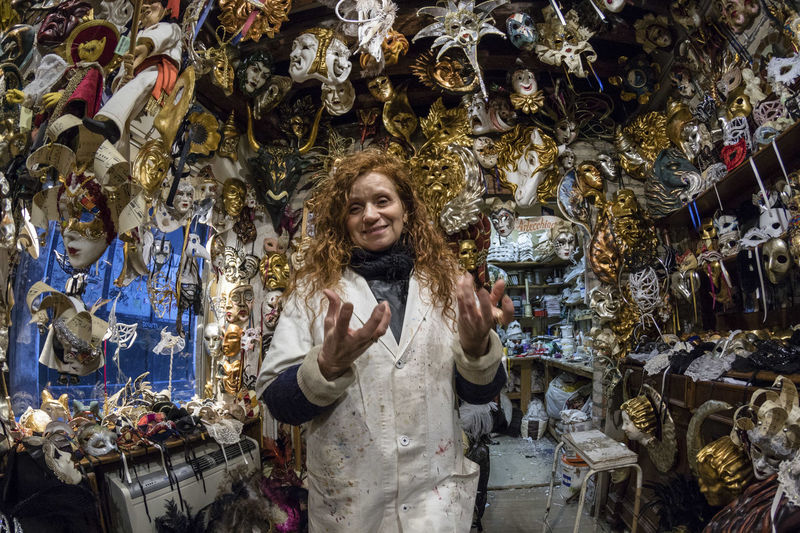 Portrait Of Woman Smiling While Standing Amidst Masks In Store