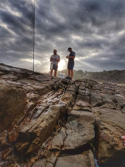 Low angle view of friends on rock against sky