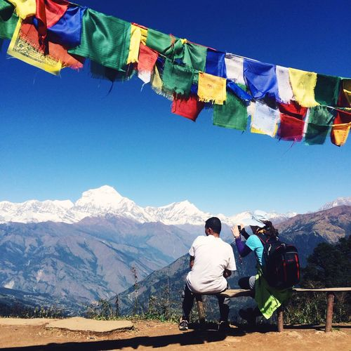 Rear view of people sitting on bench by himalayas against sky