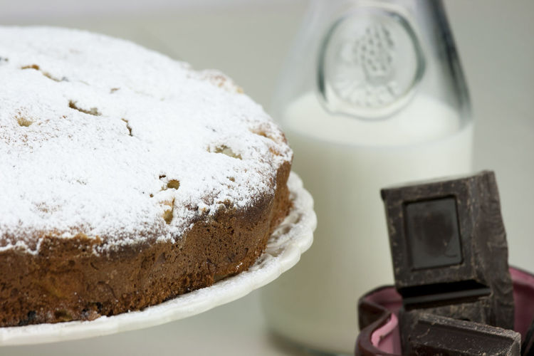 Close-up of cake with milk and chocolate bars on table