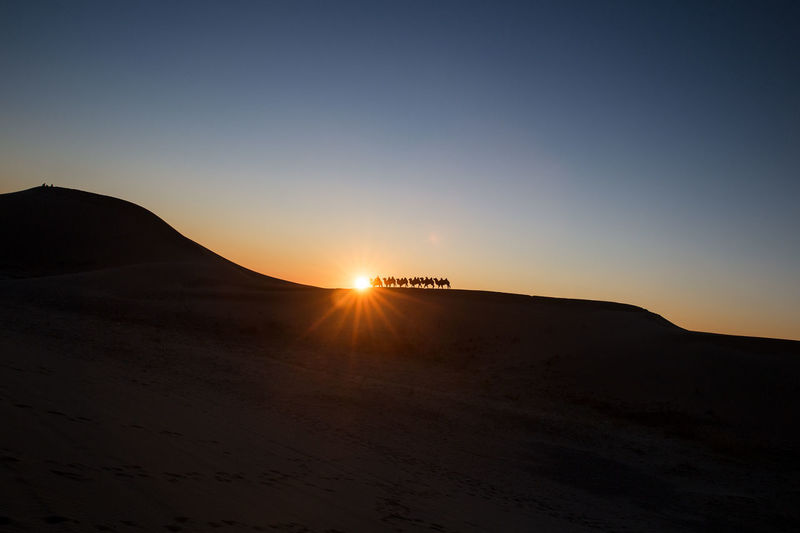 Scenic view of silhouette desert against clear sky during sunset
