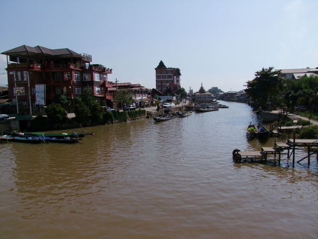 Nyaung Shwe Canal to Inle Lake Architecture Blue Sky Canal Clear Sky Composition Distant View Hotels Myanmar Narrow Boats No People Nyaung Shwe Outdoor Photography Ripples In The Water Sunlight And Shadows Tourism Tourist Attraction  Tourist Destination Town Travel Destination Tree Village Water