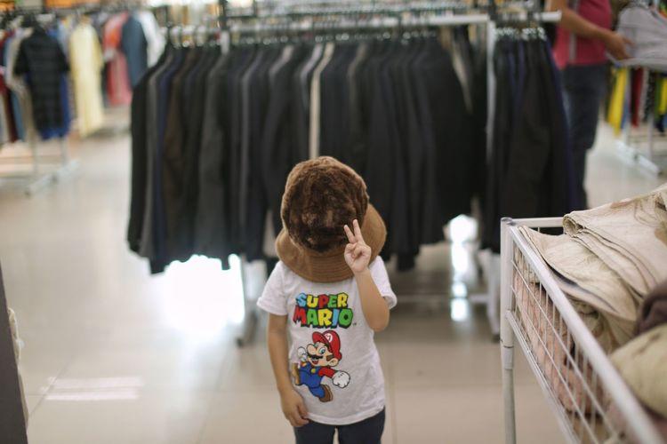 Kid with big hat in bundle shop