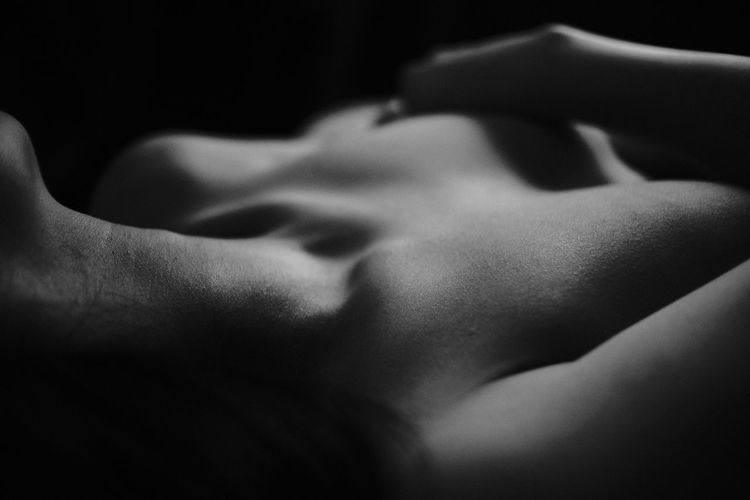 Close-up of shirtless woman against black background