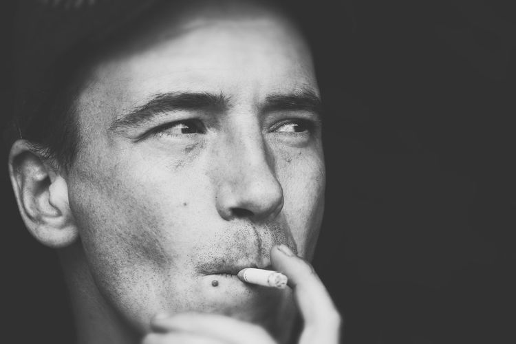 Close-up of thoughtful young man smoking against black background