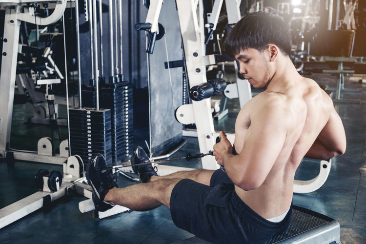 Shirtless young man exercising gym