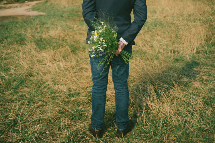 Low section of bridegroom holding bouquet while standing on grassy field in park