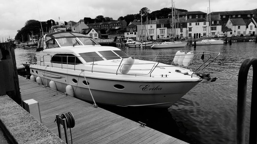 A Black And White Photography of a Beautiful Boat Moored at Weymouth Harbour United Kingdom . Featuring Nautical Vessel Harbor Sea Transportation Mode Of Transport Water Yacht Luxury Beach Day Outdoors People Sky Sailing Ship Yachting Commercial Dock Boats⛵️ Houses Holiday