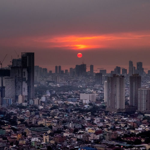 Aerial View Of Buildings In City During Sunset