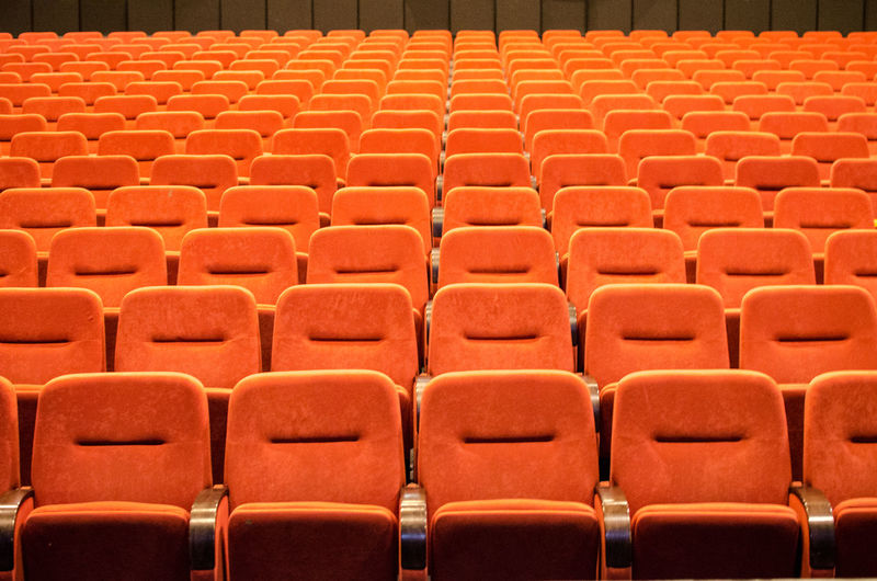 Full frame shot of orange empty chairs in theater