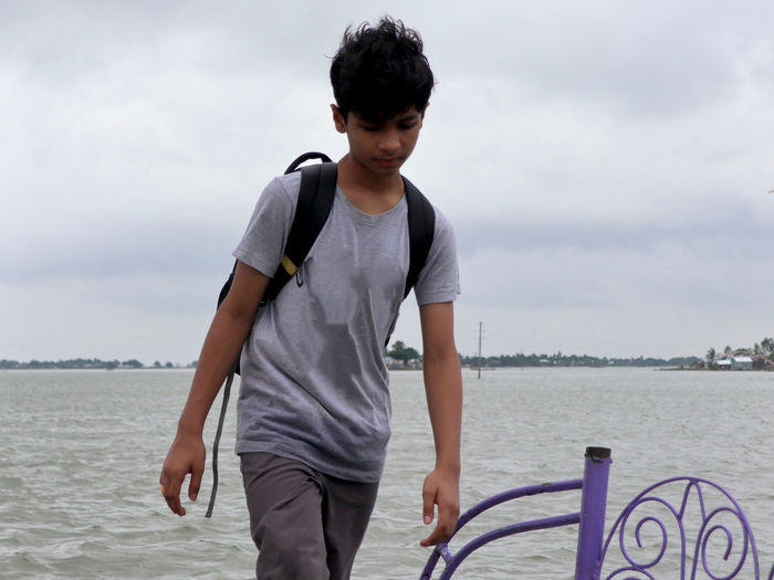 Young man standing by sea against sky