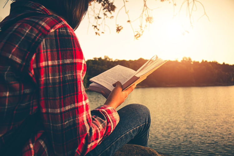 Man holding book while sitting by lake against sky during sunset