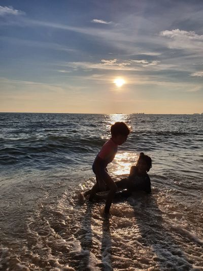 Siblings Playing In Sea Against Sky During Sunset