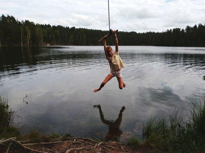 Full length of girl swinging over lake against cloudy sky in forest