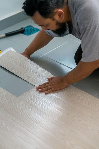 High angle view of man putting hardwood on floor