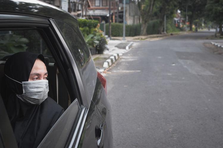 Woman wearing hijab looking through car window