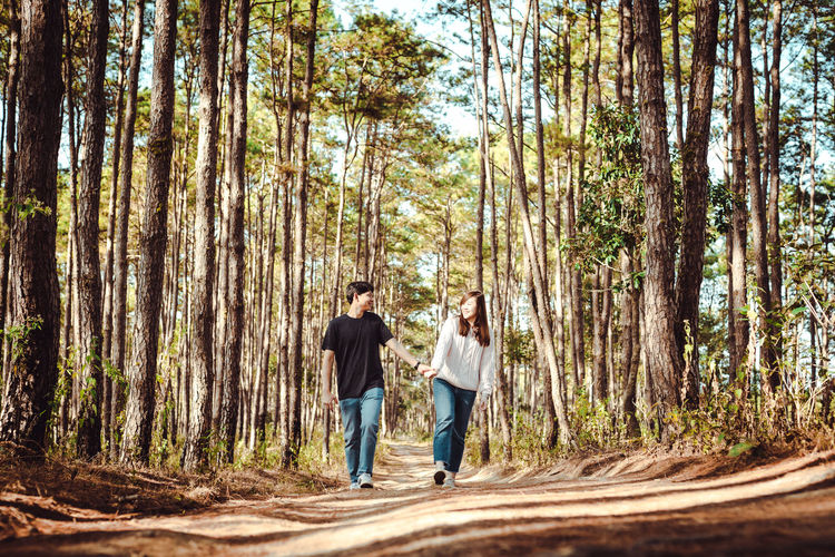 Full length of couple walking on road amidst trees in forest
