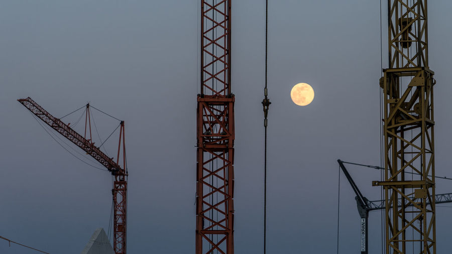 Low angle view of crane against sky at dusk