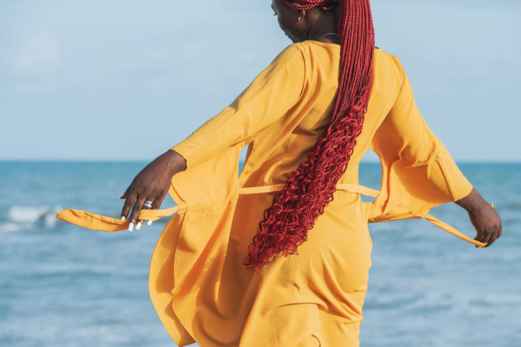 African woman wearing orange suit with long red hair standing by the sea at a sunset in accra