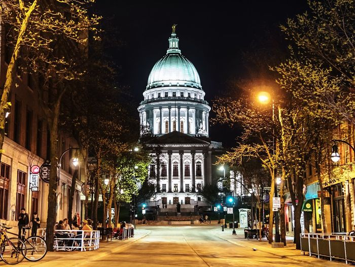Madison, Wisconsin: The state Capitol building viewed from State street. Student Life University College Campus Nightlife State Street Madison Wisconsin Capitol Building Built Structure Architecture Building Exterior Night Illuminated Dome City Travel Outdoors Government Tourism History Building Tree