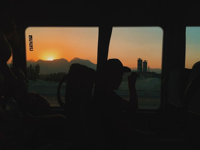 Silhouette people seen through car window during sunset