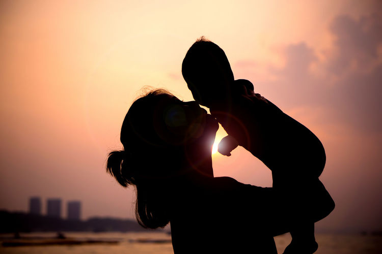 Silhouette Woman Playing With Son At Beach Against Sky During Sunset