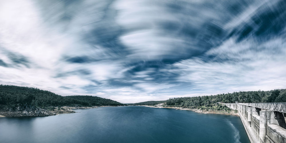 Scenic view of dam against sky with clouds.