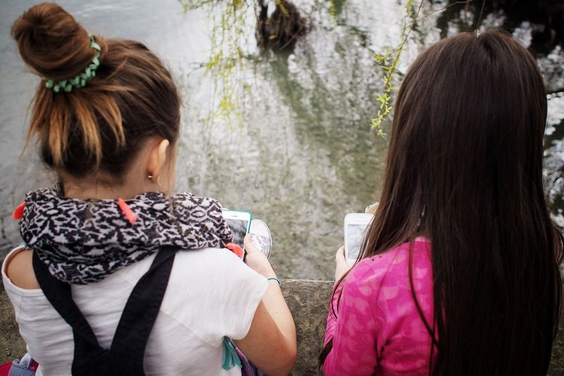 Rear View Of Women Using Mobile Phones