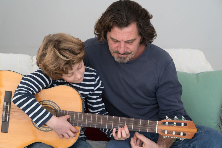 Father teaching guitar to son