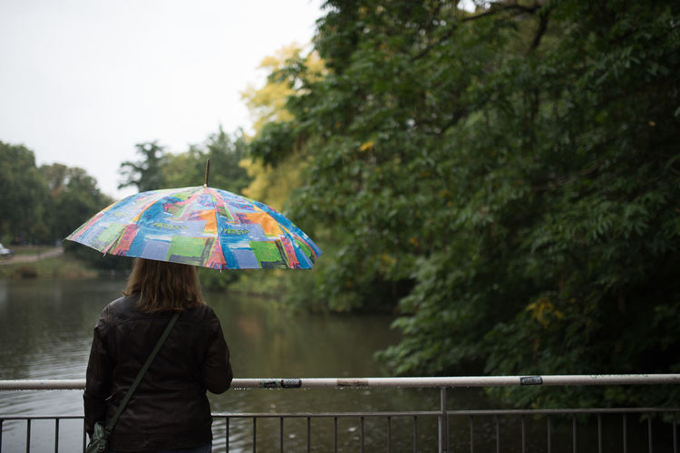 Woman with umbrella standing against lake