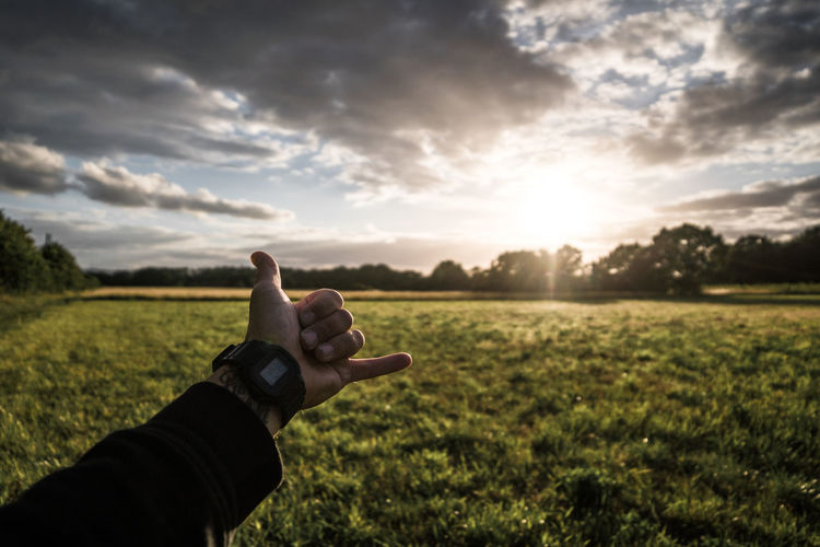 Cropped hand gesturing shaka sign over agricultural field against sky
