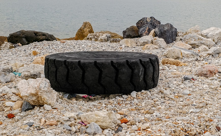excavator tire on the seashore Excavator Seashore Beach Beauty In Nature Day Nature No People Outdoors Poluted Earth Rock - Object Sand Sea Sky Tire Track Tranquility Water