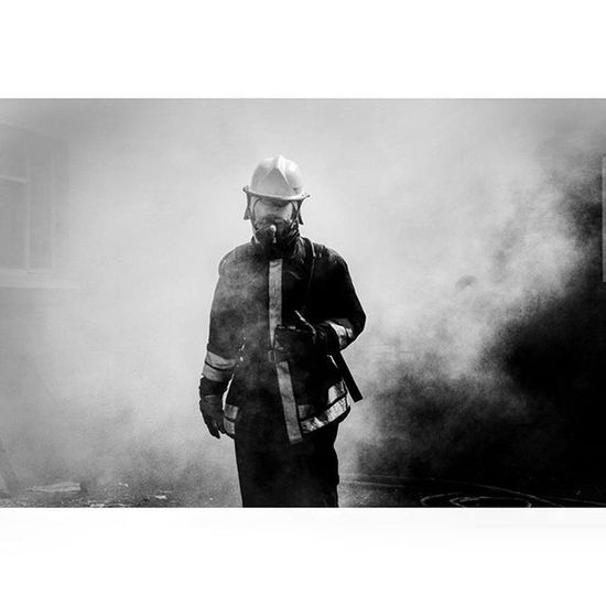 BLOEMFONTEIN, FREE STATE, SOUTH AFRICA: A firefighter comes walking through smoke during a structure fire in Bloemfontein. Firefighter Fire Heroes Smoke Fightingfires Cool Blackandwhite Photojournalist Work News Photojournalism Takingpictures Lovephotography  Eye4photography  Mycameraandi Canon Canon600D