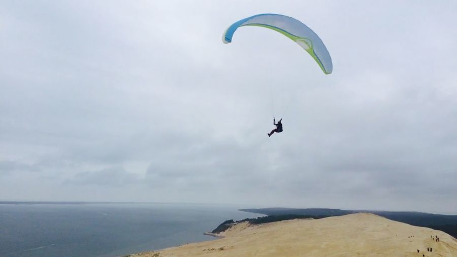 Low angle view of paragliding over sea against sky