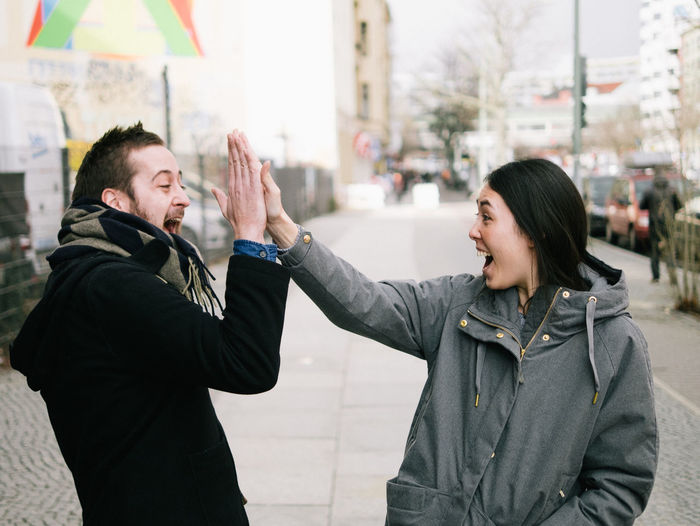 Excited friends giving high-five on sidewalk in city