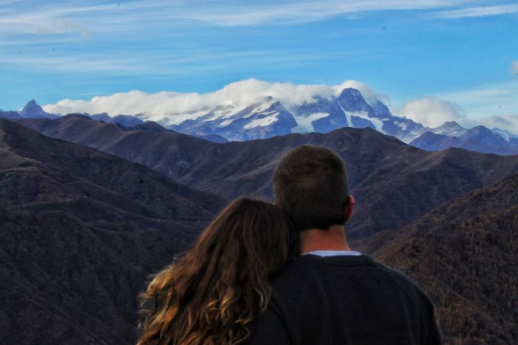 Rear view of couple looking at mountains against sky