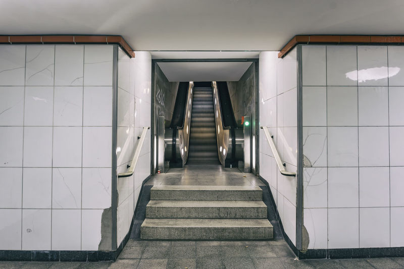 Berlin, Germany, October 10, 2018: Escalator at Underground Railway Station Berlin Germany 🇩🇪 Deutschland Horizontal No People Outdoors Color Image Indoors  Architecture Built Structure Absence Illuminated Diminishing Perspective Wall - Building Feature Tile White Color Subway Station Underground Station  Escalator Technology Convenience Mode Of Transportation Steps And Staircases Exit Steel Metal