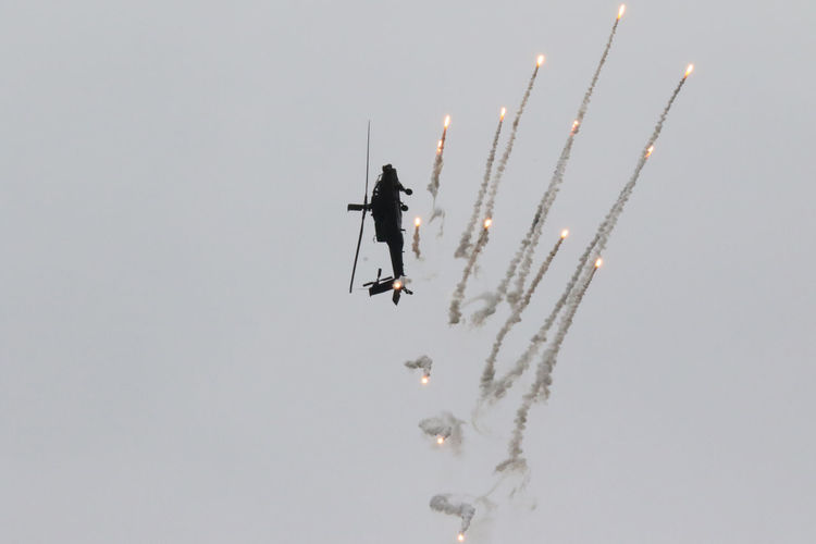 Adventure Apache Helicopter Beauty In Nature Day Flares Leisure Activity Lifestyles Low Angle View Mid-air Motion Nature Outdoors Season  Sky Tranquility Unrecognizable Person Weather